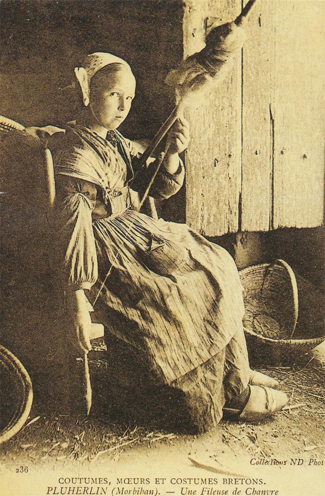 Carte postale de la fin du XIXe siècle représentant une fille de Bretagne (France) fabriquant des fils de chanvre.
